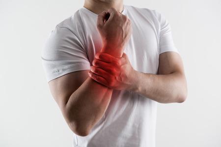 broken wrist: Hombre con la mu�eca rota. Joven masculino masaje mano herida de dolor. Concepto de tratamiento de las fracturas de emergencia y el hueso.