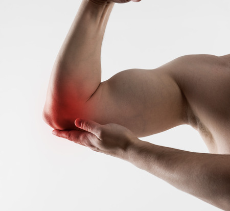 hurt: Muscle strain and stretch. Muscular man suffering from sore biceps pain. Concept of health care and medicine.