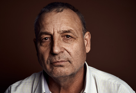 Close-up portrait of contemplative senior caucasian man thinking about something and looking at camera. Stock Photo