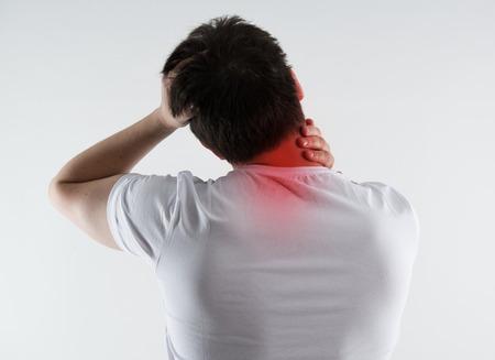若い男性は、痛みで首をマッサージします。うなじ傷害。背骨の問題。