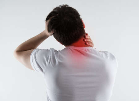 stoop: Young male massaging his neck in pain. Nape injury. Spine problem. Stock Photo