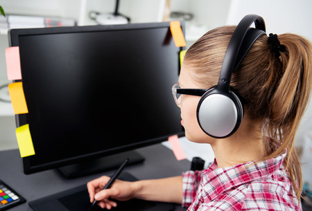 digitizer: Young graphic artist in headphones working with stylus and graphic tablet in the office. Modern female designer with color swatch samples on the desk. Stock Photo