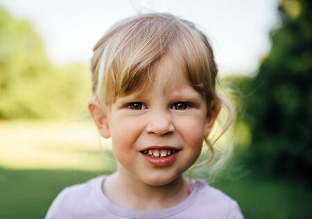 grinning: Adorable blond girl grinning looking at camera in the park