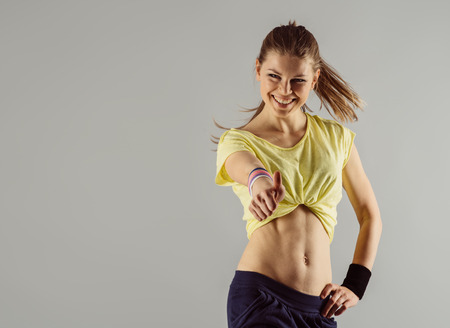Smiling woman trainer in fitness gym doing exercise showing thumb up. Healthy and active lifestyle. Standard-Bild