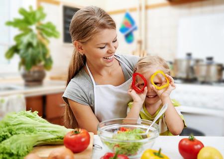 cocineros: Sonriendo mamá y su hija linda que se divierte cocinando la cena vegetariana. Pequeño niño que juega con los anillos de pimienta mientras prepara la ensalada.