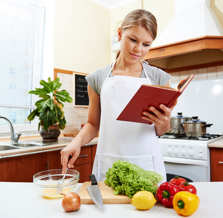 vegetable cook: Concentrated female reading recipe book and cooking meal. Young housewife wearing white apron preparing vegetable dish in the house.