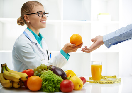 Smiling doctor nutritionist giving orange to male patient sitting at the desk with colorful fruits and vegetables. Concept of natural remedy and healthy lifestyle. Stock Photo