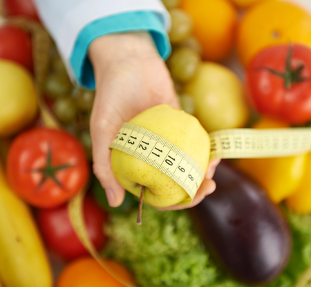Doctor dietitian holding apple and measuring tape over eco nutrition background. Concept of health care, diet and vegetarian food.