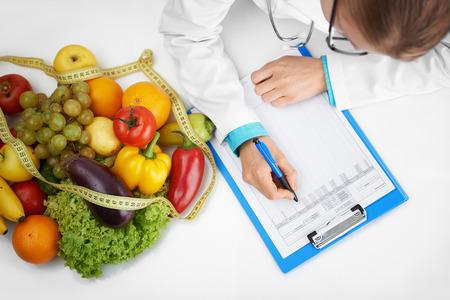 病院で机に座ってケース開発フォームを書く医者のセラピスト。女性栄養士は、患者に食事療法を処方します。