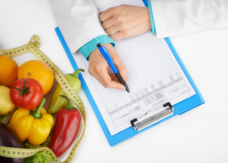 dietician: Close-up of doctor diettian hands with pen prescribing treatment. Female physician filling medical history form in the office. Stock Photo