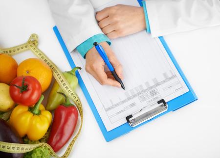 Close-up van de arts diettian handen met pen voorschrijven behandeling. Vrouwelijke arts vullen medische geschiedenis vorm in het kantoor.