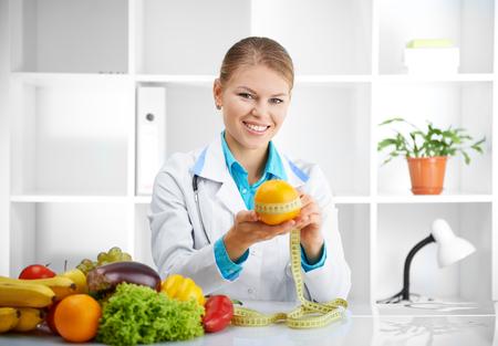 estilo de vida saludable: Retrato del doctor alegre nutricionista medición de naranja en su oficina. Concepto de alimentos naturales y estilo de vida saludable.