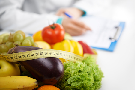obesity: Healthy nutrition concept. Close-up of fresh vegetables and fruits with measuring tape lying on doctors desk.