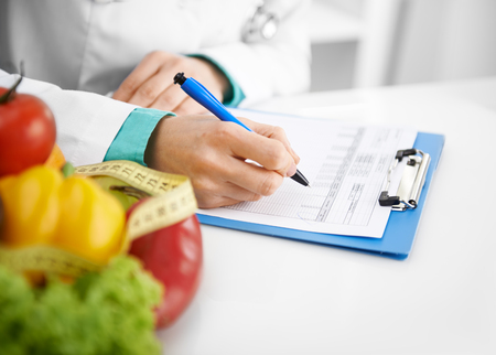 nutritionist: Doctor nutritionist writing case history in the office. Young woman dietitian prescribing recipe.