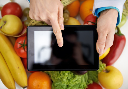 learning online: Close-up of doctor nutritionist pointing at smth on digital tablet screen. Weight loss and health care. Stock Photo