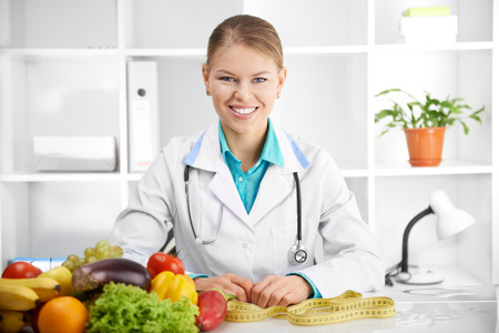 obesity: Happy smiling female dietitian in uniform with stethoscope at workplace. Young woman doctor sitting at the desk with eco food.