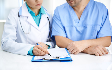 Portrait of two medical colleagues analyzing test result together in hospital. Young doctors team in uniforms working with documents at the desk.