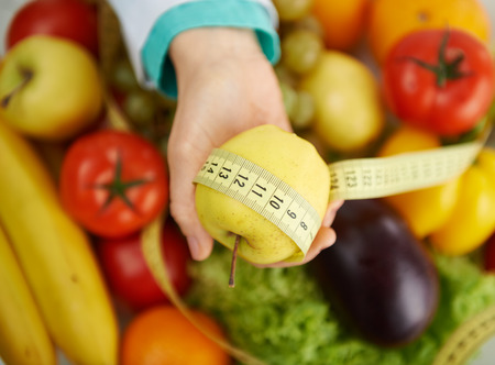 dietitian: Doctor dietitian holding apple and measuring tape over eco nutrition background. Concept of health care, diet and vegetarian food.