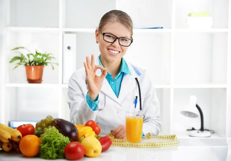 """행복 한 미소 의사 영양사 카메라를보고 """"확인""""기호를 게재. 건강한 체중 감소 및 비만 치료의 개념. 스톡 콘텐츠"""