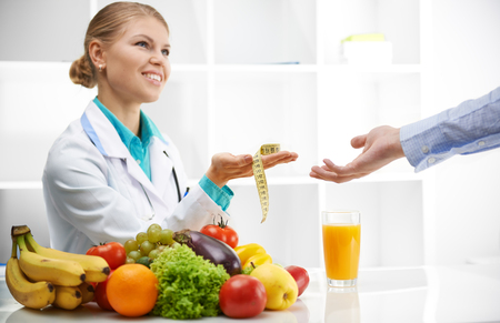 juice fresh vegetables: Portrait of smiling female dietitian giving measuring tape to patient. Slimming concept.