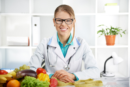 Smiling female dietitian sitting at the table with colorful fruits and vegetables in clinic. Concept of diet, lose weight and healthcare. Stock Photo