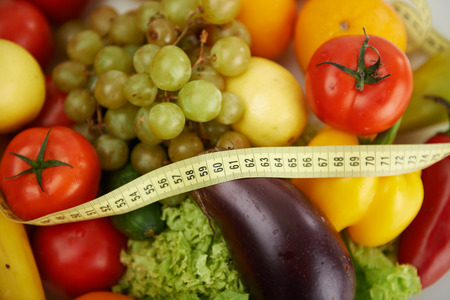 slim: Slim down concept. Close-up of measuring tape lying on fresh and healthy fruits and vegetables.
