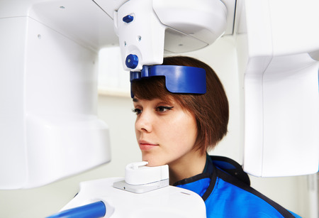 Close-up of woman patient doing panoramic teeth x-ray in dental clinic. Concept of medical technology and equipment.