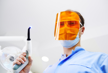 filling equipment: Portrait of male dentist in protective mask standing over patient with ultraviolet light equipment. Teeth filling, whitening and hygiene concept.