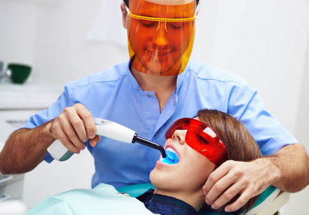 molar: Male dentist treating females molar with ultraviolet light in clinic. Young woman sitting in chair with open mouth wearing protective glasses.