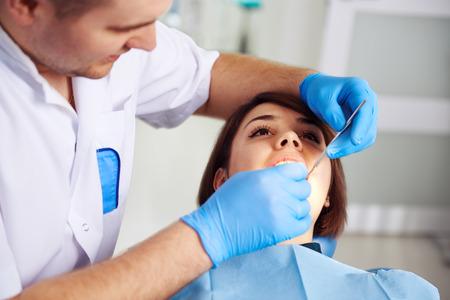dentist: Mujer joven que visita a su dentista. Paciente femenina sentada en silla en la clínica dental con la boca abierta, tomando el tratamiento. Concepto de examen de los dientes y curación de la enfermedad. Foto de archivo