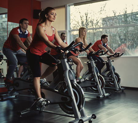 Young active people exercising in spinning class. Group of fit people doing sport in the gym. Standard-Bild