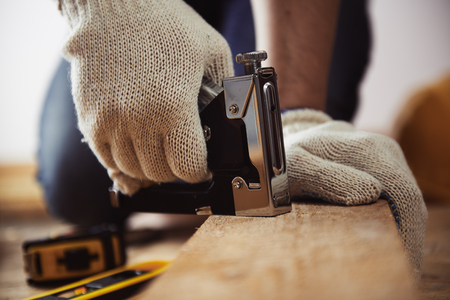 staplers: Close-up of craftsman hands working with construction instruments on the floor in his workshop . Stock Photo