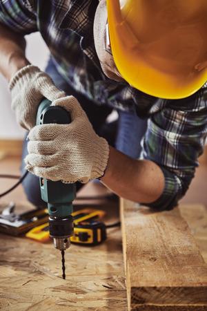 ヘルメット作業スタジオで木材をドリルで若い便利屋。工芸と技術の概念。