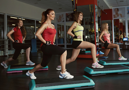 step by step: Step course in the gym. Group of female doing aerobics fitness for losing weight.