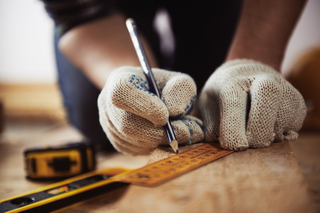 職人のクローズ アップは、定規と鉛筆で木の板を測定保護手袋の手します。木工品や改修のコンセプトです。