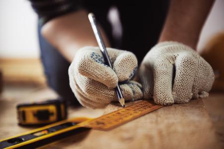 Het close-up van vakman dient beschermende handschoenen in die houten plank met heerser en potlood meten. Houtwerk en renovatieconcept. Stockfoto