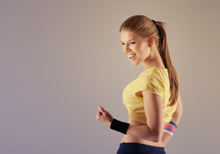 jazz modern: Aerobics fitness woman. Happy smiling female dancer posing in studio with copy space.