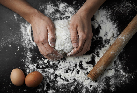 Chef hands kneading raw dough on the board in bakery. Woman cook preparing bread or pastry.