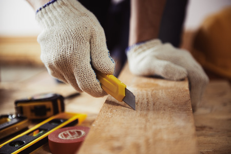 contractor: Male contractor working with wooden plank and cutter on the floor. Close-up of mature craftsmans hands in protective gloves with building tools. Stock Photo
