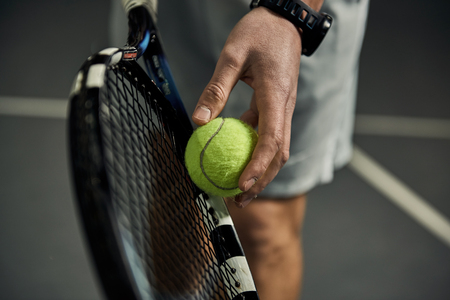 Close-up of male hand holding tennis ball and racket. Professional tennis player starting set. Archivio Fotografico