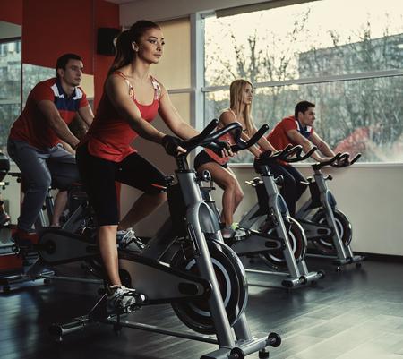 motion: Unga aktiva människor som utövar i spinningpass. Grupp passar människor som gör idrotten i gymmet.