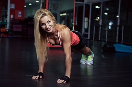 aerobics class: Pretty smiling fitness trainer doing push-ups in the gym. Young sportswoman exercising at aerobics class. Healthcare and weight loss concept.