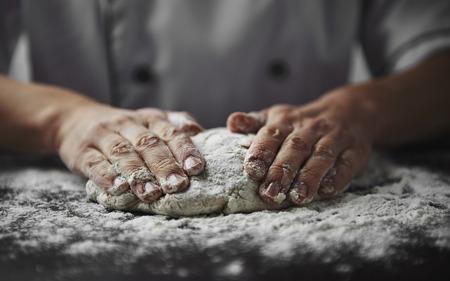 Close-up Hände der Frau Bäcker den Teig auf schwarzem Karton mit Mehl Pulver geknetet wird. Konzept des Backens und Patisserie.