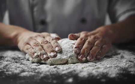 dough: Close-up of woman baker hands kneading the dough on black board with flour powder. Concept of baking and patisserie. Stock Photo