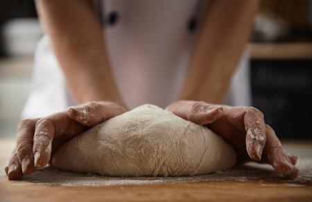 masa: Primer plano de manos de cocinero hembra amasando masa para pizza o pasta en la cocina. Preparación de alimentos saludables.