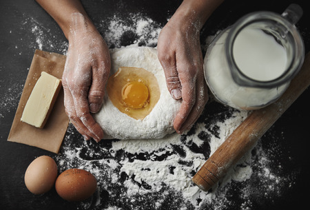 Woman hands kneading dough on the black board with eggs, milk, butter and flour. Healthy breakfast preparation concept. 版權商用圖片 - 55392547
