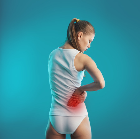 spinal disks: Kidney pain. Young female touching her painful loin. Health care and medical treatment.