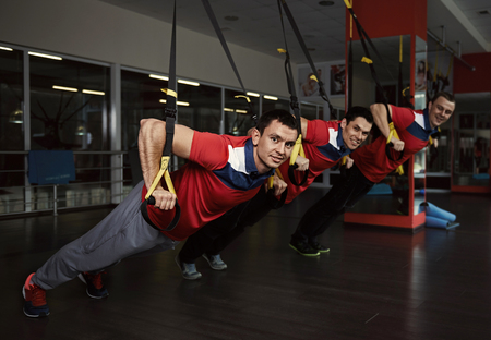 loop: Trx. Gymnastics exercise. Young athletic Caucasian boys training with fitness straps in the gym. Stock Photo