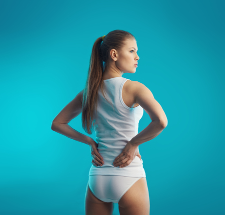 lumbago: Lumbago. Back pain. Young attractive female holding her sore loin over blue background.