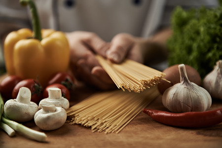 Woman chef cooking italian pasta with garlic, pepper, mushrooms, tomatoes and greens on wooden table. Banque d'images